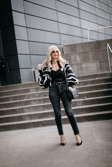 With black top, dark colored jeans, chain strap bag and black pumps