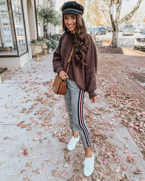 With brown loose sweater, black embellished cap, brown leather bag and white sneakers