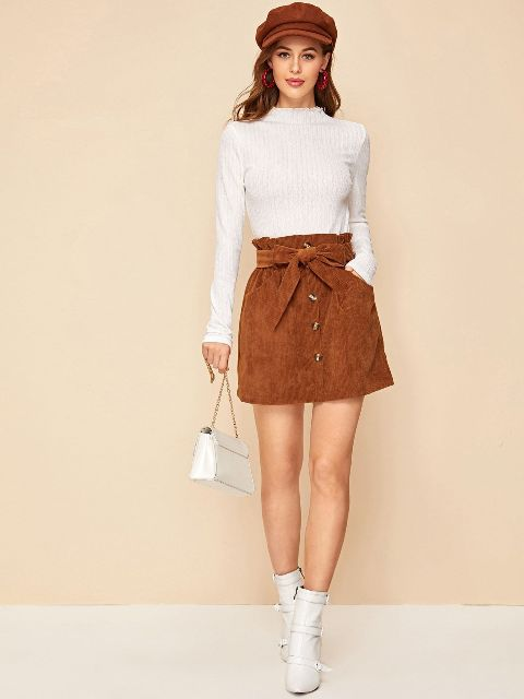 With brown suede cap, white long sleeved shirt, chain strap bag and white ankle boots