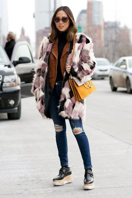 With brown suede jacket, black turtleneck, distressed jeans, platform shoes and yellow bag