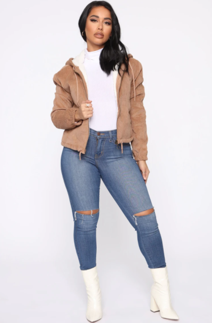 With distressed skinny jeans, white mid calf boots and white turtleneck