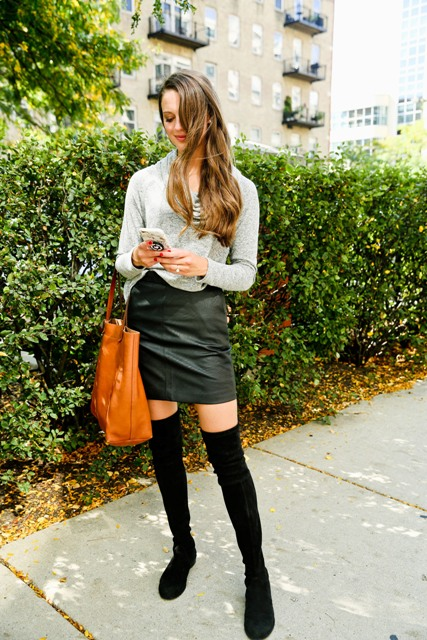 With gray shirt, brown tote bag and black leather mini skirt