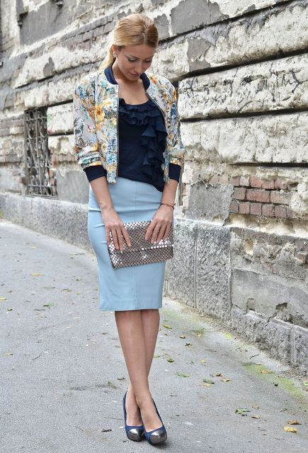With navy blue ruffled blouse, floral printed bomber jacket, silver clutch and silver and blue shoes