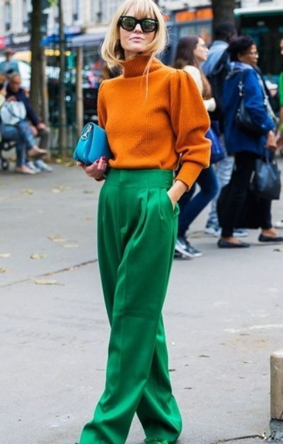 With orange turtleneck sweater, blue clutch and green shoes
