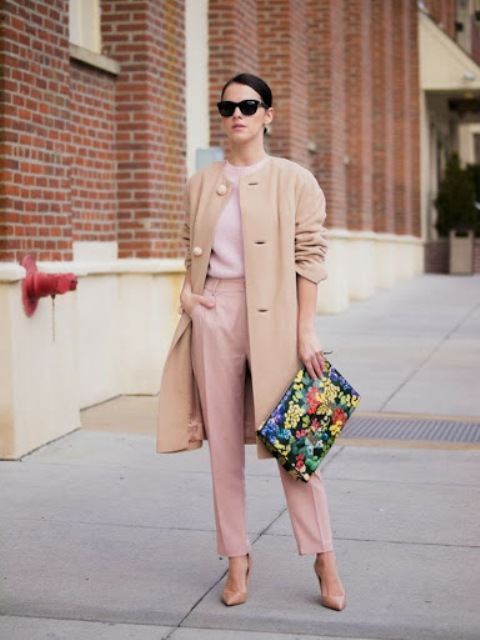 With pale pink sweater, pale pink trousers, floral printed clutch and beige pumps