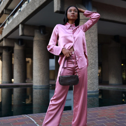 With pink satin button down shirt and leather bag