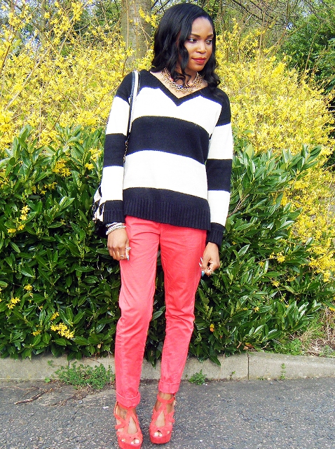 With pink trousers, bag and platform shoes
