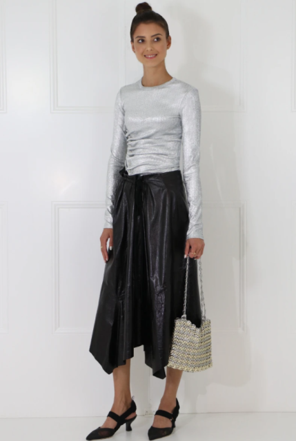 With silver shirt, chain strap bag and low heeled shoes