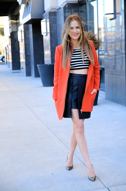With striped crop top, orange coat and leather pumps