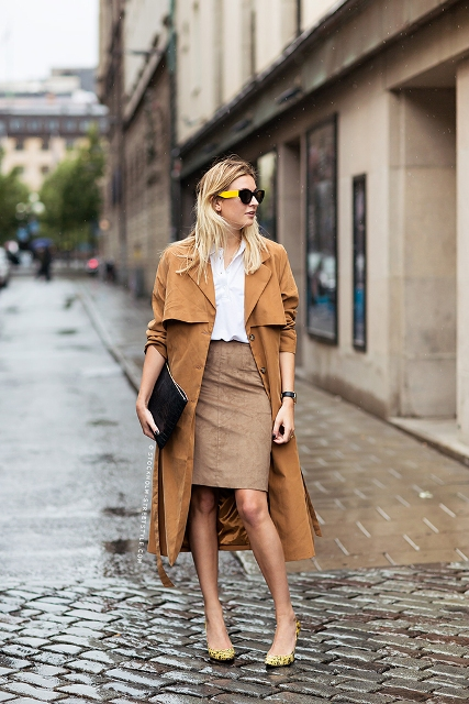 With white shirt, brown midi coat, black clutch and printed shoes