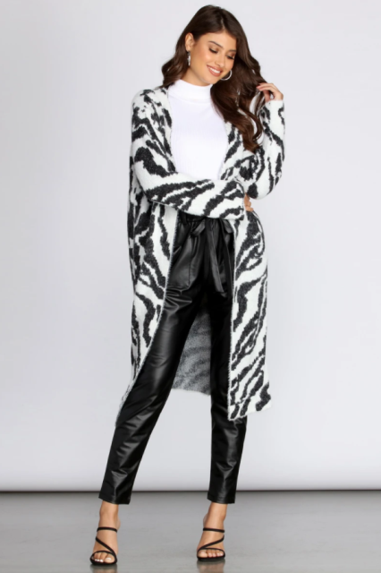 With white turtleneck, black leather belted pants and black high heels