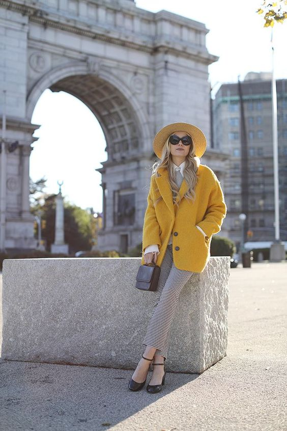 a Parisian chic look with grey gingham pants, a grey top, black shoes, a yellow coat and a hat plus a black bag
