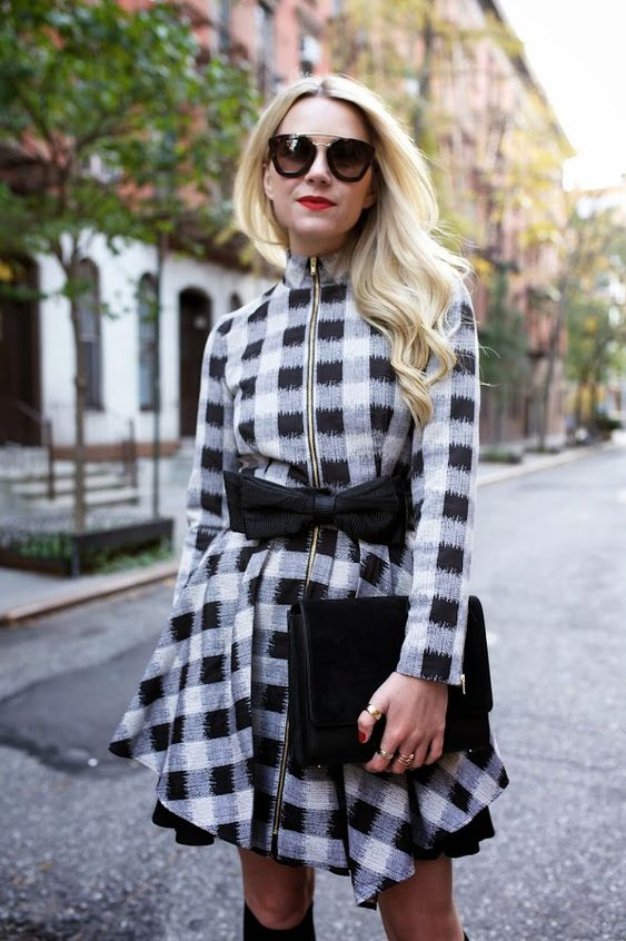 a black and white check A-line zip dress with a bow on the waist, black boots and a clutch