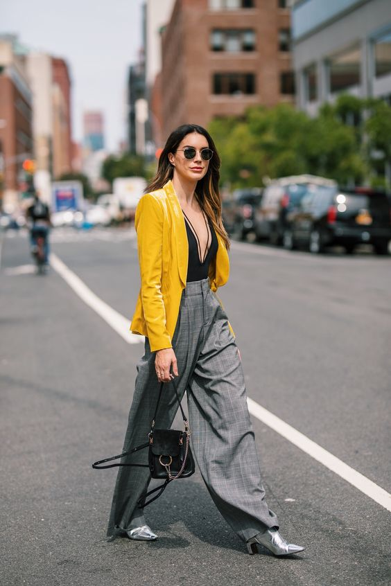 a black bodysuit with a plunging neckline, a yellow blazer, grey plaid wideleg pants, silver boots