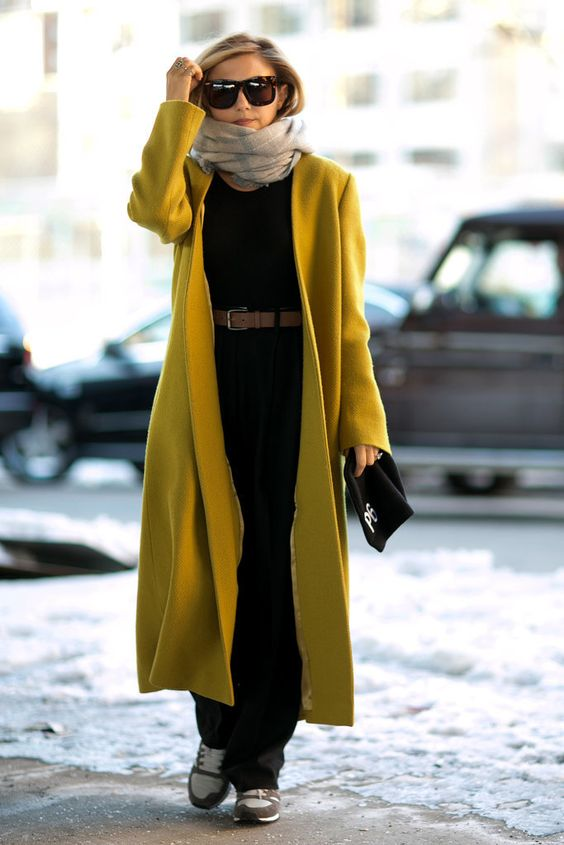 a black jumpsuit, grey trainers, a brown belt, a mustard coat, a scarf and a black cap