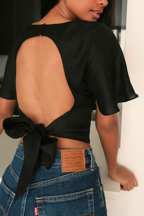a black open back crop top with a bow on the back and classic blue jeans for a jaw-dropping date look
