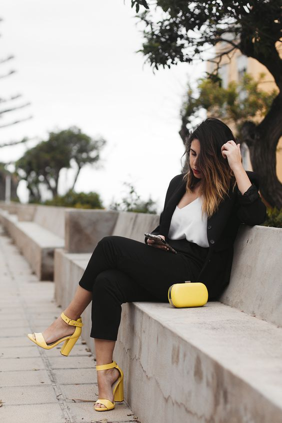 a black pantsuit, a white top, yellow ankle strap block heels and a matching clutch for a party or date
