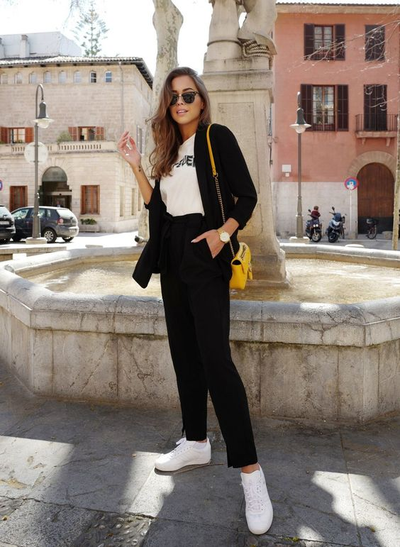 a black pantsuit with paperbag waist pants, a white printed tee, white sneakers and a yellow bag