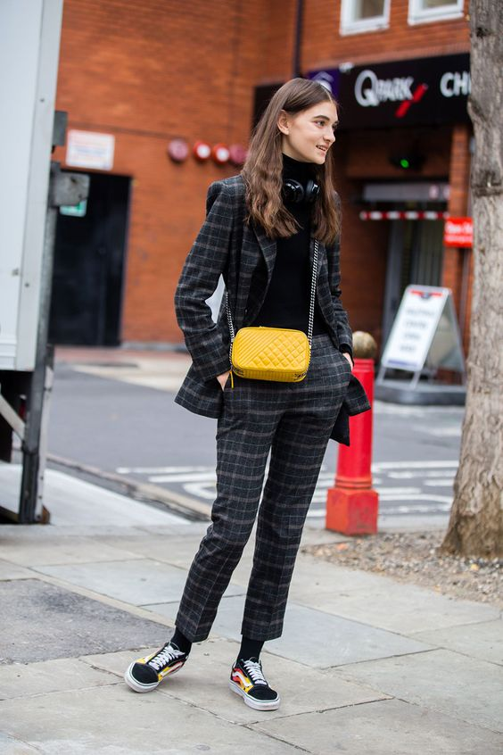a black plaid pantsuit, a black turtleneck, black sneakers, a honey yellow crossbody bag for work