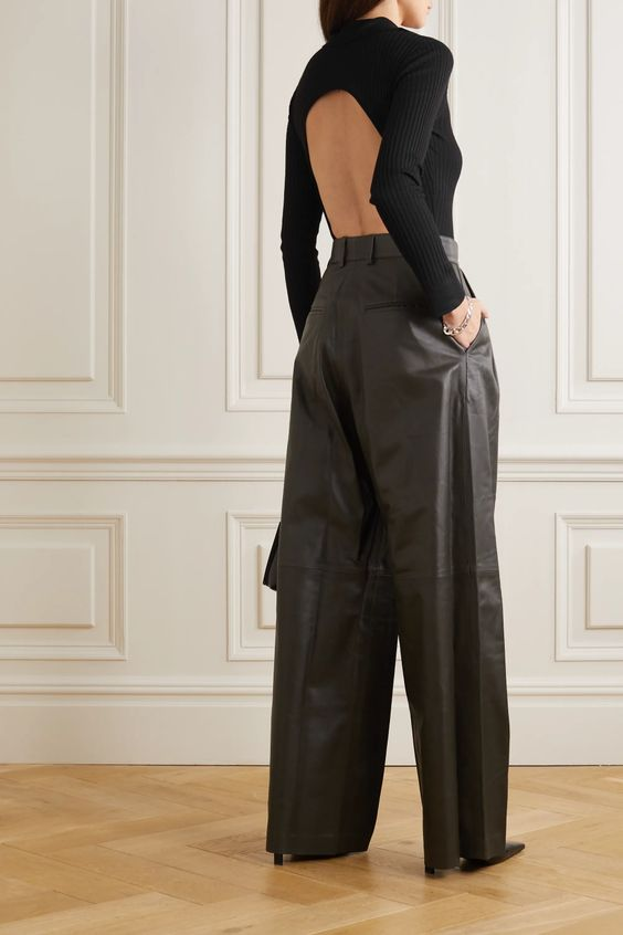 a black ribbed knit bodysuit with an open back and long sleeves, wideleg leather trousers