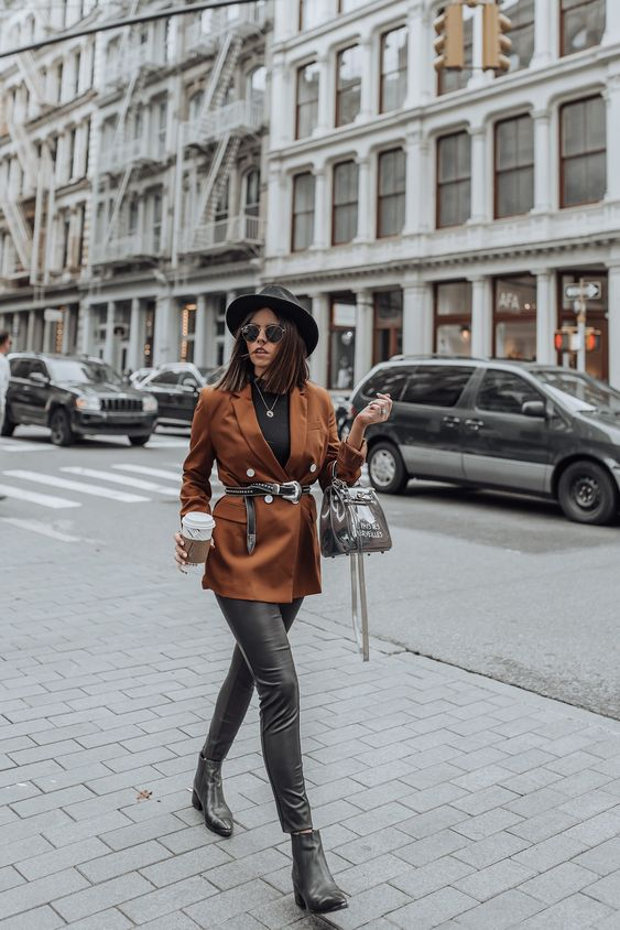 a black tee, a rust colored blazer, black leather leggings, black booties, a black hat and a silver bag