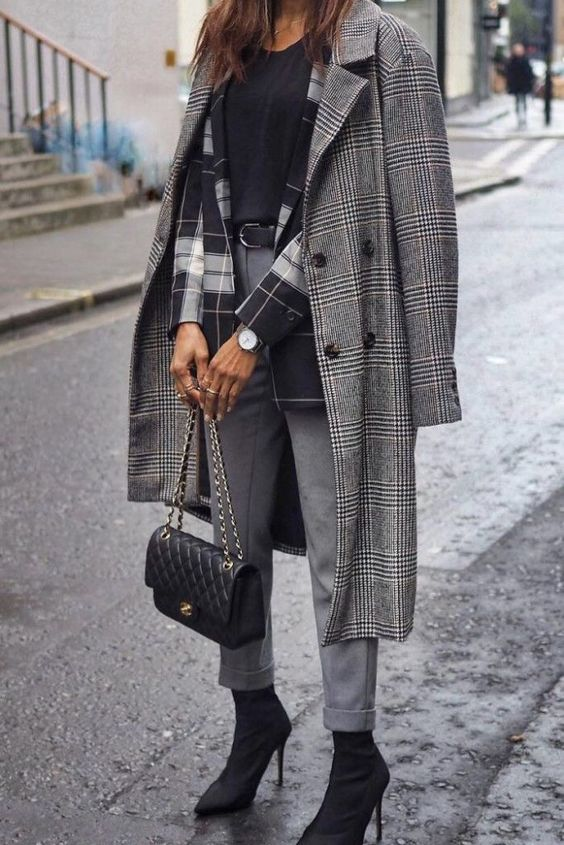 a black tree, a plaid blazer, grey trousers, a grey plaid coat, black sock boots and a black bag