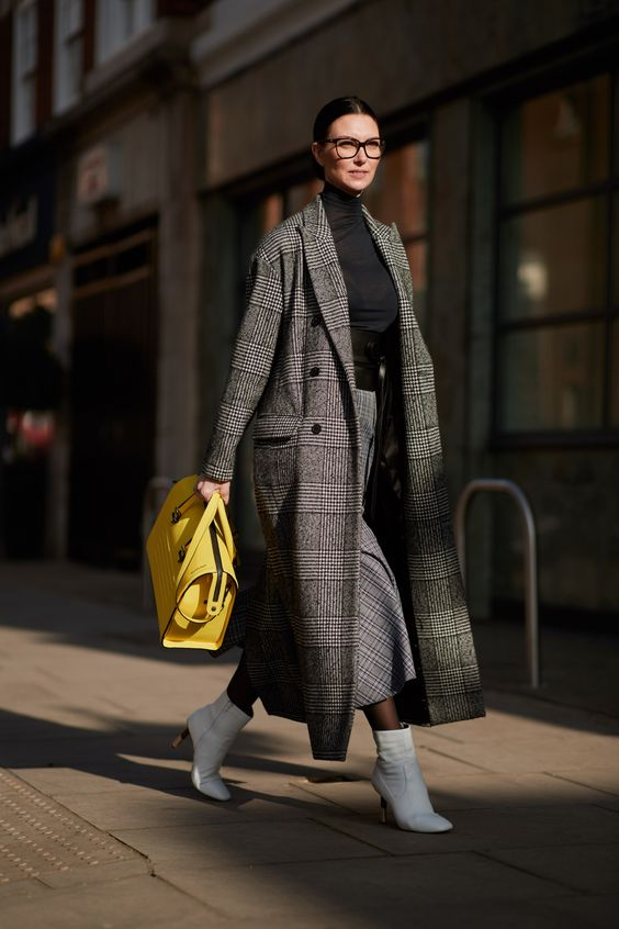 a black turtleneck, a grey plaid midi skirt, white boots, a grey plaid midi coat, a bright yellow bag