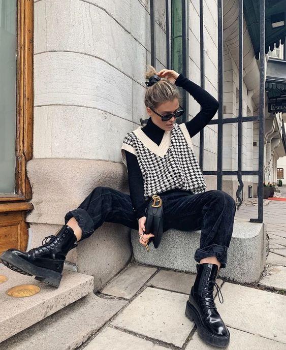 a black turtleneck, a trendy printed V neck vest, black corduroy pants, black boots and a bag