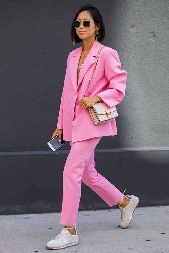 a bold and trendy look with a barbie pink suit with oversized pants, neutral trainers and a bag for spring