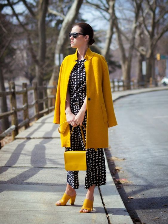 a bold spring look with a printed black and white jumpsuit, yellow heels, a yellow coat and a matching bag