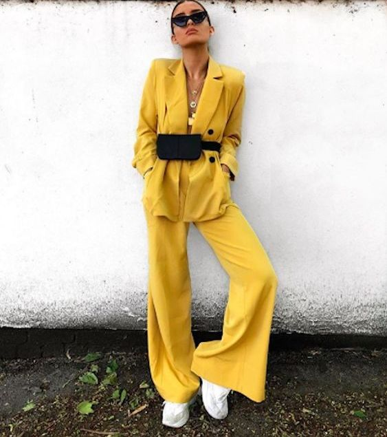a bold yellow pantsuit with wideleg pants and an oversized blazer, white trainers, a black bag and layered necklaces