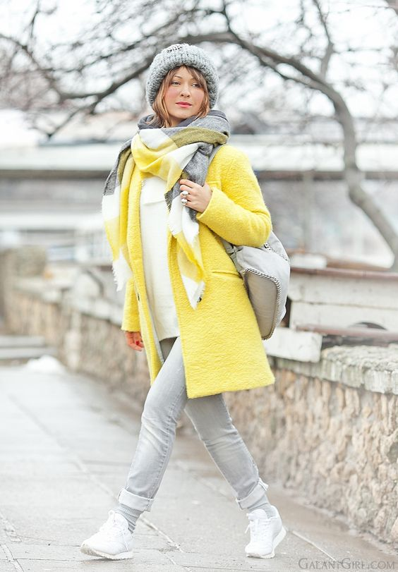a bright and trendy winter outfit with a white sweatshirt, grey jeans, grey trainers, a yellow coat, a grey bag and beanie and bold scarf