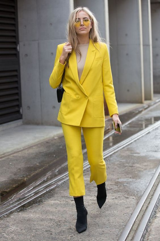 a bright spring look with a lemon yellow pantsuit, a nude top, black sock boots, a black bag