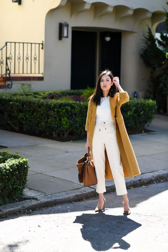 a casual look with a white tee, white jeans, grey shoes, a brown bag and a honey yellow coat