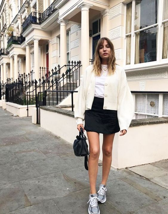 a casual outfit with a white tee, a creamy bomber jacket, a black mini skirt, grey trainers and a black bag
