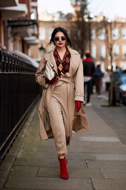 a chic and bold look with a printed jumper, tan trousers, a tan trench, red boots, gloves and a white bag