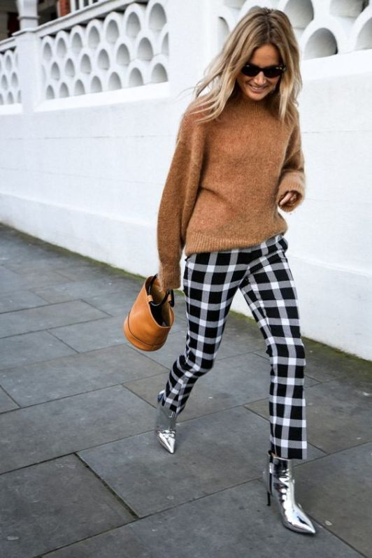 a chic outfit with a tan sweater, black and white check pants, silver boots and an amber bucket bag