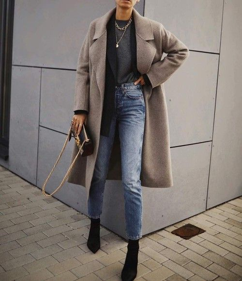 a classic layered look - a grey tee, blue jeans, a blazer blazer, a grey coat and layered necklaces plus black sock boots