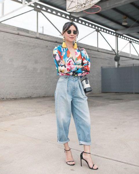 a colorful printed shirt, blue barrel jeans, black heels and a bucket bag plus tassel earrings
