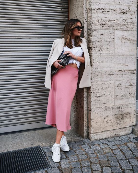 a cozy and chic look with a white tied up tee, a pink slip midi skirt, white trainers, a neutral blazer and a printed clutch