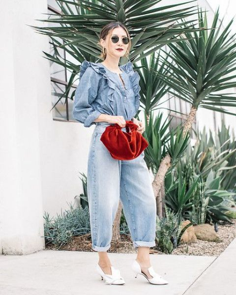 a double denim look with a shirt with ruffles, barrel jeans, white shoes and a red velvet bag