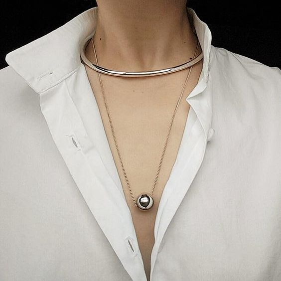 a duo of necklaces – a metal choker and a metal sphere on a thin chain look very chic and very trending