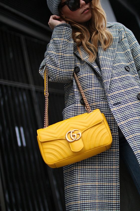 a cozy look with a plaid coat and a yellow bag