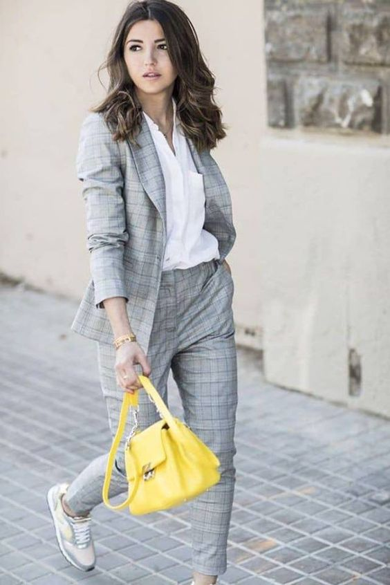 a grey plaid suit, a white shirt, grey trainers and a lemon yellow bag for a colorful accent