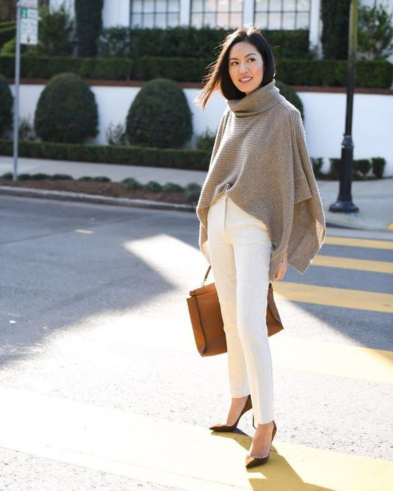 a grey poncho sweater, white trousers, rust-colored shoes and a matching bag for transitional time