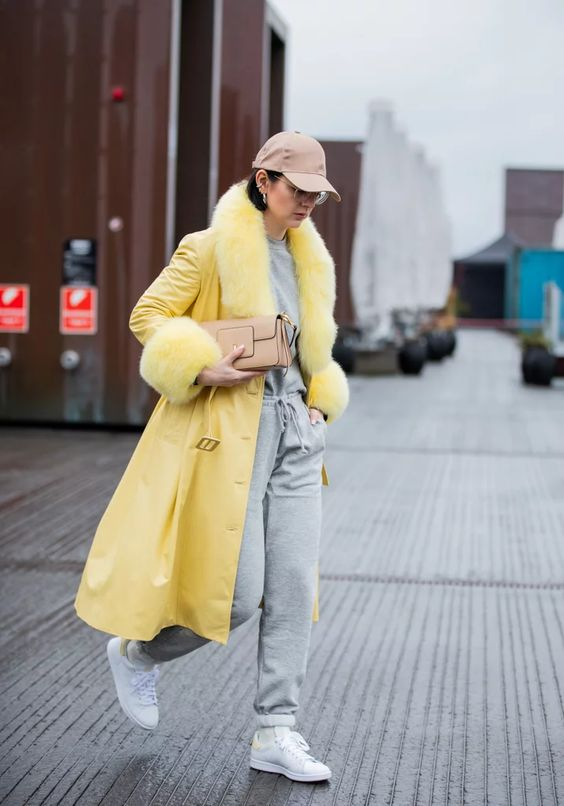 a grey sweatshirt, grey joggers, white sneakers, a yellow coat with faux fur and a cap
