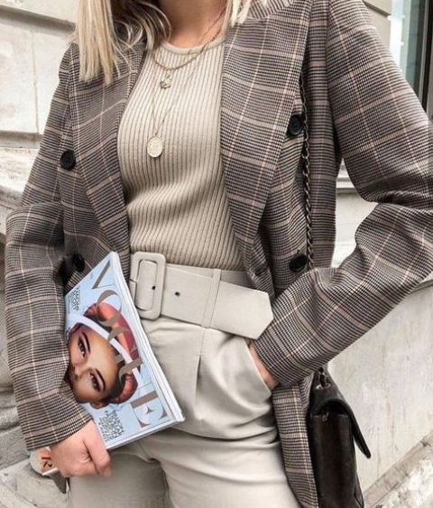 a grey top, grey pants with a wide belt, a plaid oversized blazer, a brown bag