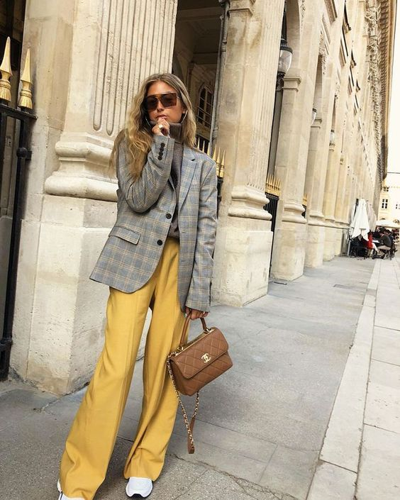 a grey turtleneck, a grey plaid blazer, marigold pants, white trainers and a brown bag