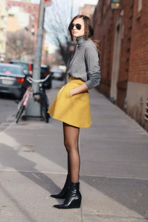 a grey turtleneck, a yellow A line mini, black tights and black boots will compose a look for right now