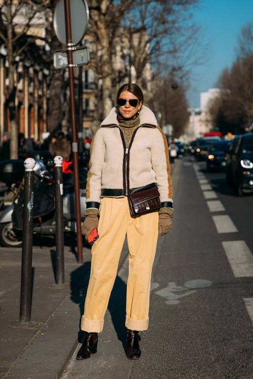 a grey turtleneck, yellow pants, a white and black faux fur jacket, black boots and a burgundy bag